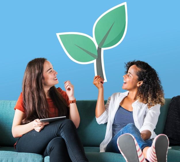 Mujeres alegres sosteniendo un icono de planta Foto gratis