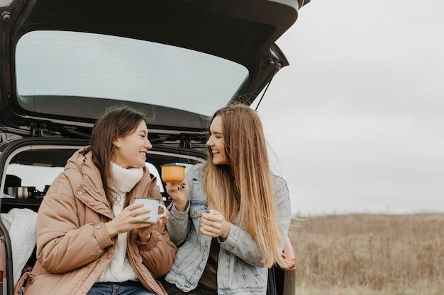 Mujeres de ángulo bajo bebiendo té caliente Foto gratis