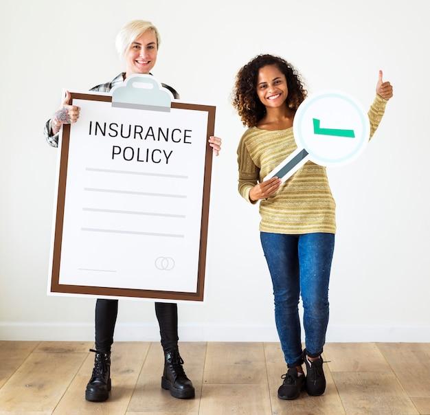 Mujeres con artes de papel de pólizas de seguros Foto gratis