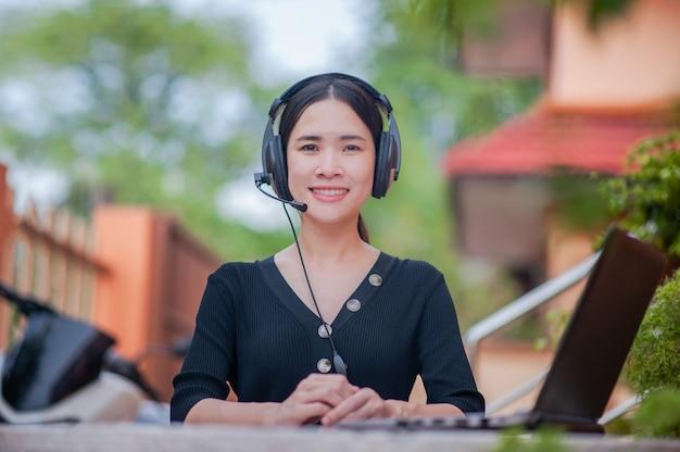 Las mujeres asiáticas de belleza son un centro de atención telefónica que ofrece un nuevo trabajo normal desde casa Foto Premium