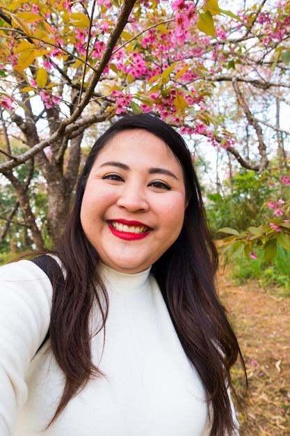 Mujeres asiáticas con cabello largo y negro toman selfie sonriendo, retrato con flores Foto Premium
