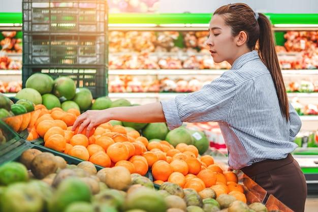 Las mujeres asiáticas de compras de alimentos saludables verduras y frutas en el supermercado Foto Premium