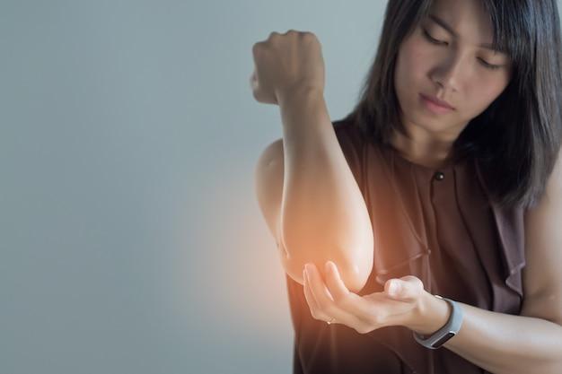 Mujeres asiáticas dolor de codo, dolor de codo de niña sobre fondo blanco. Foto Premium