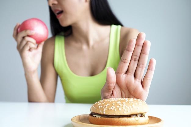 Las mujeres asiáticas empujan el plato de hamburguesas y eligen comer manzanas para una buena salud. Foto Premium