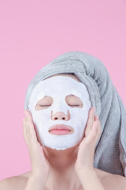 Las mujeres asiáticas hermosas están utilizando la cara de la mascarilla en la hoja en un fondo rosado. Foto gratis