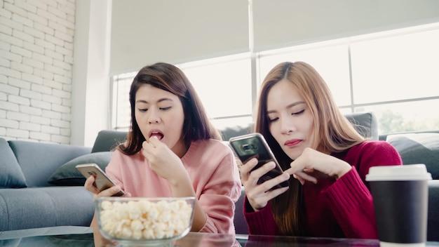 Mujeres asiáticas que usan teléfonos inteligentes y comen palomitas en la sala de estar en casa Foto gratis