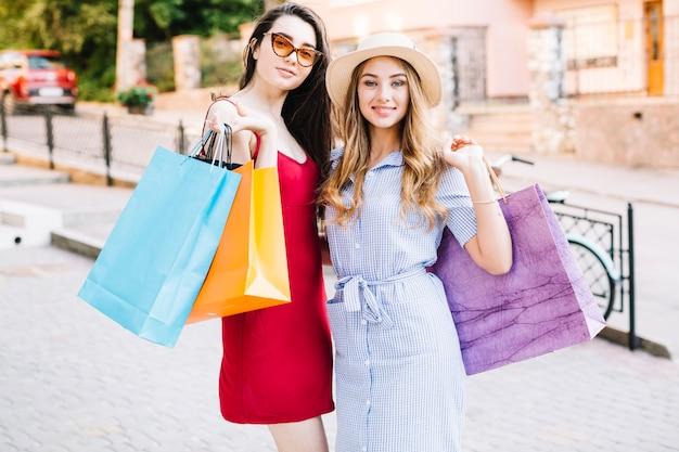 Mujeres atractivas posando con bolsas de papel Foto gratis