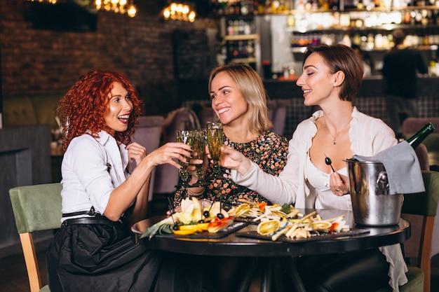 Mujeres en el bar que tienen charla dinking cocktails Foto gratis