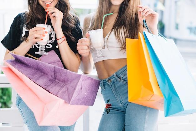 Mujeres con batidos y bolsas de papel Foto gratis