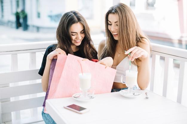 Mujeres con batidos mirando bolsa de papel Foto gratis