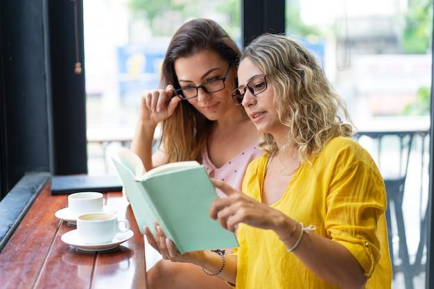 Mujeres bonitas que leen el libro de texto y que beben el café en café Foto gratis