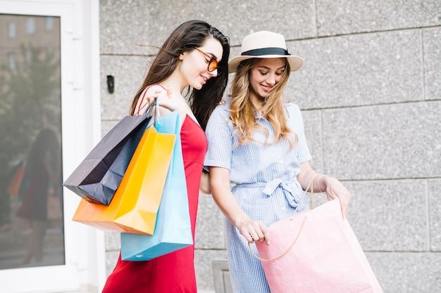 Mujeres bonitas que miran la bolsa de papel Foto gratis