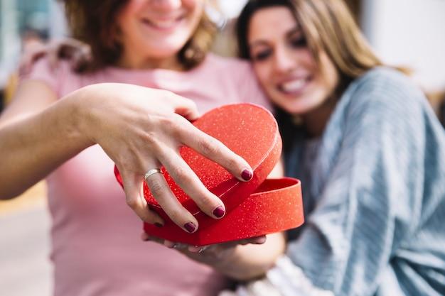 Mujeres borrosas abriendo la caja en forma de corazón Foto gratis