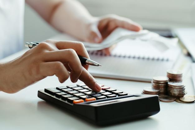 Las mujeres calculan las facturas domésticas en casa. usando la calculadora en la oficina moderna y comprobando el saldo y los costos. mujeres haciendo trámites para pagar impuestos Foto Premium