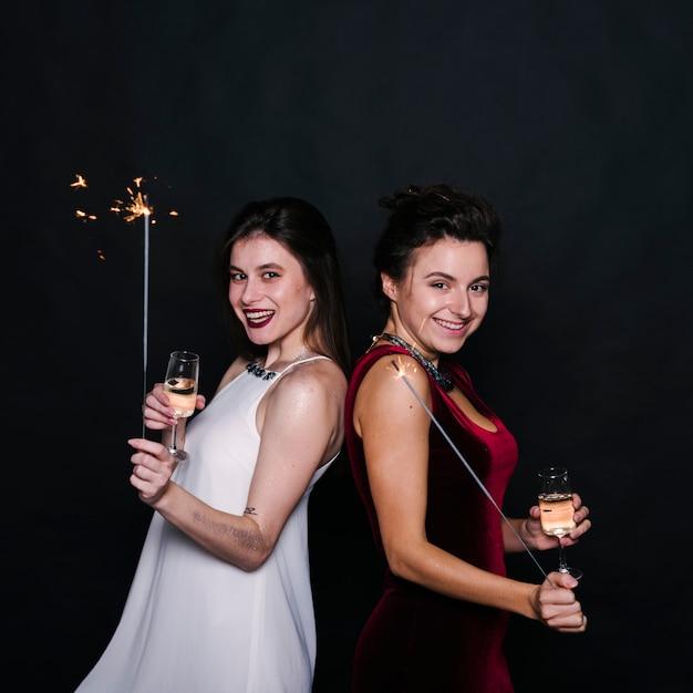 Mujeres con copas de champán y bengalas. Foto gratis