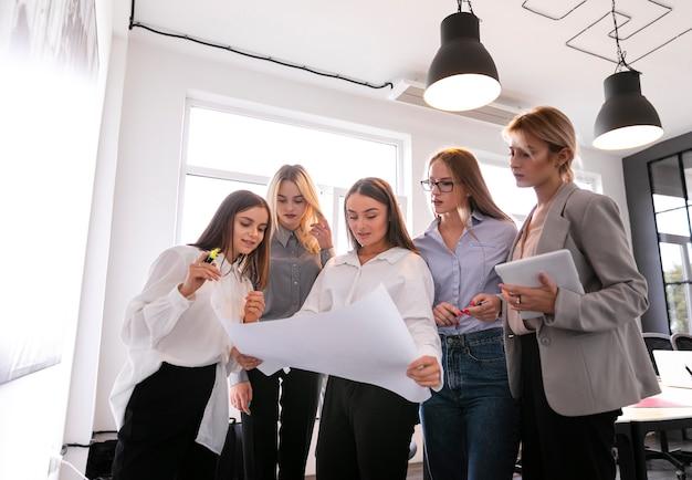 Mujeres corporativas de ángulo bajo que controlan planes Foto gratis