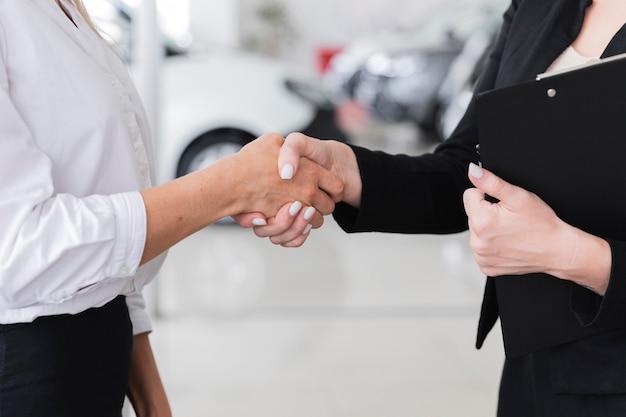 Mujeres dándose la mano en la sala de exhibición de autos Foto gratis