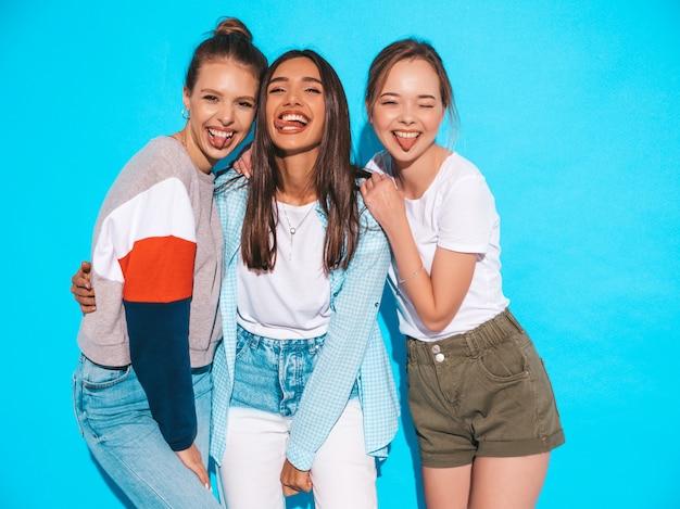 Mujeres despreocupadas atractivas que presentan cerca de la pared azul en estudio. modelos positivos divirtiéndose y abrazándose. muestran lengua Foto gratis