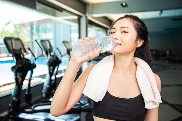 Las mujeres después del ejercicio beben agua de botellas y pañuelos en el gimnasio. Foto gratis