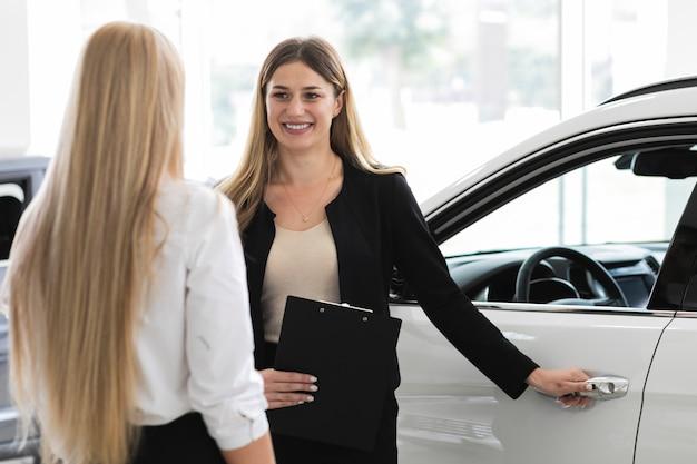 Mujeres discutiendo en la sala de exposición de automóviles Foto gratis