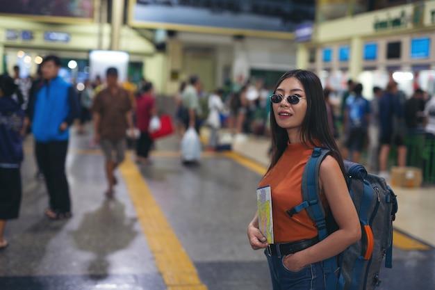 Las mujeres disfrutan viajando en el mapa a la estación de tren. Foto gratis