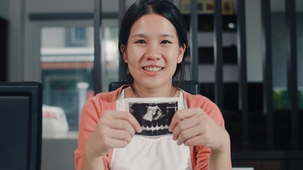 Las mujeres embarazadas asiáticas jóvenes muestran y mirando a la foto de ultrasonido bebé en el vientre. mamá se siente feliz sonriendo pacífica mientras cuide al niño sentado en la mesa en la sala de estar en casa por la mañana. Foto gratis