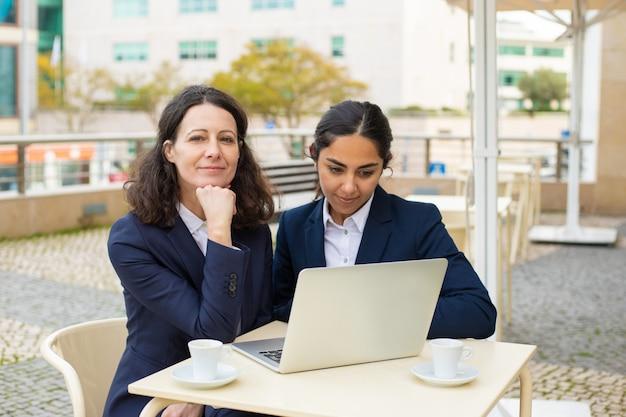Mujeres empresarias felices con laptop en café al aire libre Foto gratis