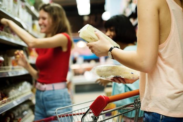 Mujeres escogiendo comida de una estantería de supermercado. Foto Premium