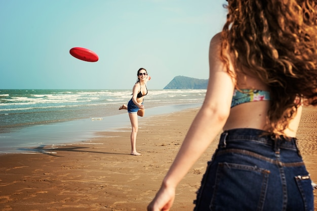 Las mujeres están jugando frisbee en la playa Foto gratis