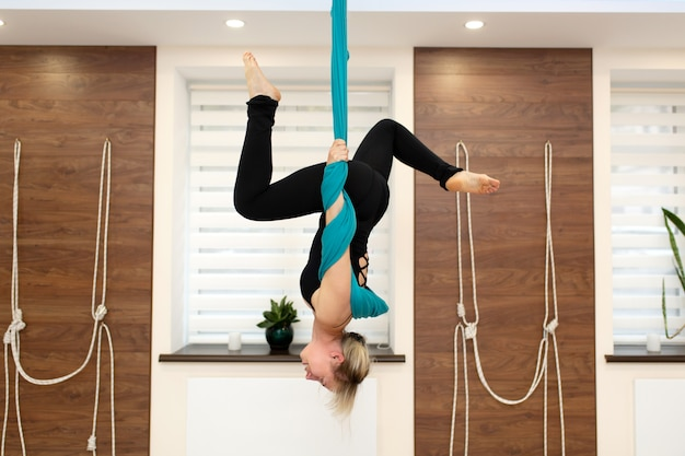 Mujeres estirando colgado boca abajo en una hamaca. volar clase de yoga en el gimnasio. estilo de vida en forma y bienestar Foto Premium
