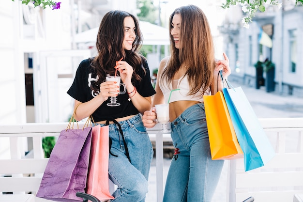 Mujeres felices con batidos después de ir de compras Foto gratis