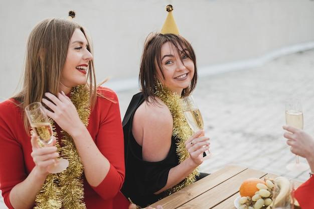 Mujeres felices en vestidos rojos y negros de fiesta en la azotea Foto gratis