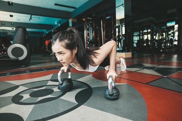Mujeres haciendo ejercicio empujando el suelo con el kettlebell en el gimnasio. Foto gratis
