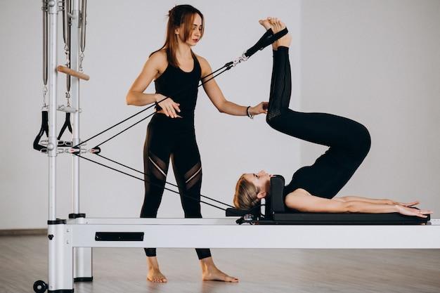 Mujeres haciendo pilates en un reformador. Foto gratis