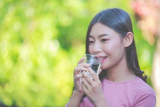 Mujeres hermosas beben agua limpia de un vaso de agua. Foto gratis