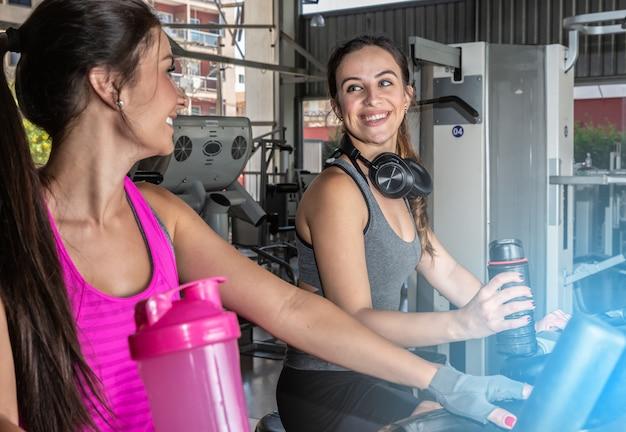 Mujeres hermosas entrenando en un gimnasio. grupo hermoso de amigos de las mujeres jovenes que ejercitan en una rueda de ardilla en el gimnasio moderno brillante. Foto Premium
