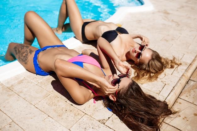 Mujeres hermosas jóvenes sonriendo, tomando el sol, relajarse junto a la piscina. Foto gratis