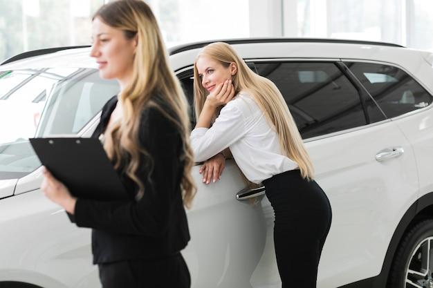 Mujeres hermosas en la sala de exposición de automóviles Foto gratis