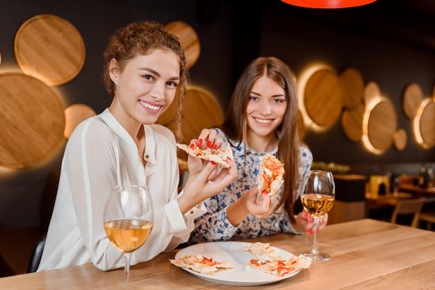 Mujeres hermosas sonriendo, posando y comiendo pizza en pizzería. Foto Premium