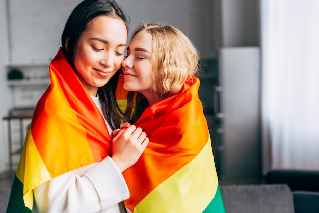 Mujeres homosexuales enamoradas envueltas en bandera arcoiris Foto gratis
