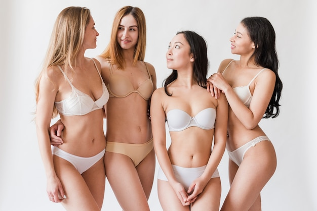 Mujeres jóvenes alegres en ropa interior mirando el uno al otro Foto gratis