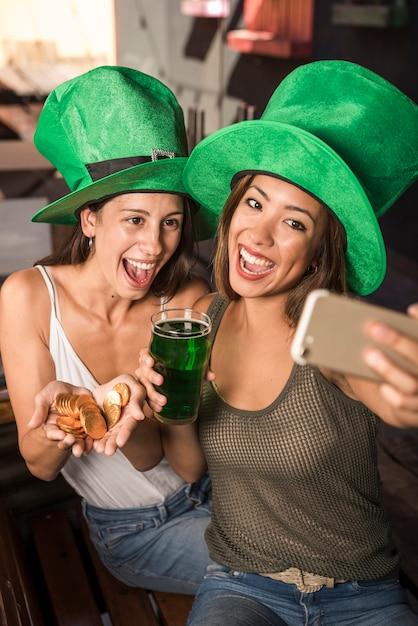 Mujeres jóvenes alegres con vaso de bebida y monedas de oro que toman selfie en un teléfono inteligente Foto gratis