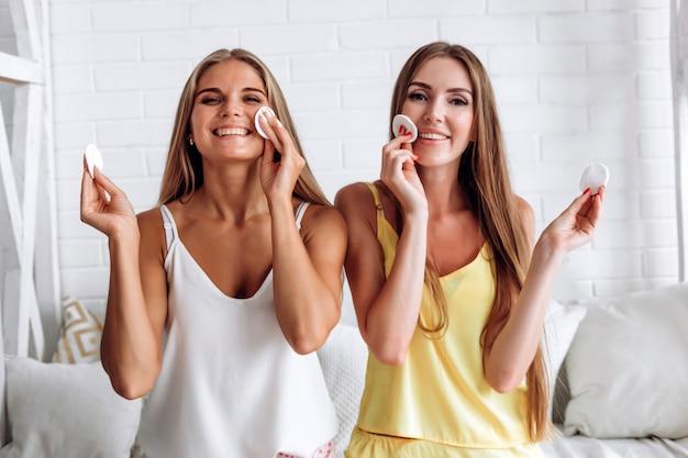 Mujeres jóvenes con almohadillas de algodón cerca de su cara. cuidado de la piel, spa y tratamientos de belleza. desmaquillante. Foto Premium