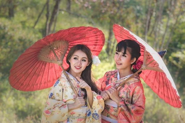 Las mujeres jovenes asiáticas que llevan el kimono japonés tradicional que sostiene el paraguas rojo en el flor de cereza parquean. Foto Premium