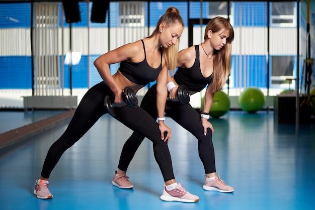 Las mujeres jóvenes atléticas un entrenamiento en el gimnasio. Foto Premium