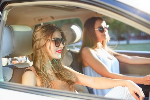 Mujeres jóvenes en el auto sonriendo Foto gratis