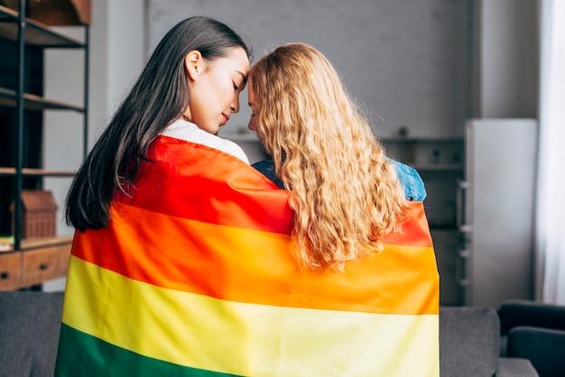 Mujeres jóvenes enamoradas cubriendo en bandera de arcoiris Foto gratis