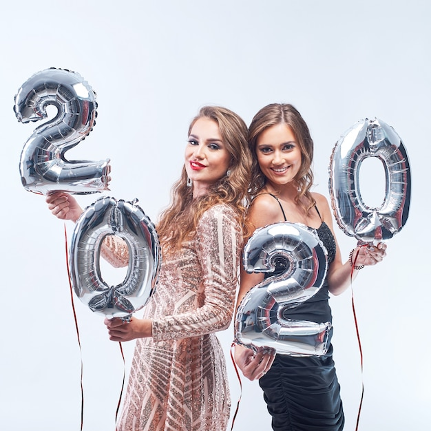 Mujeres jóvenes felices con globos metálicos 2020 en blanco. Foto Premium