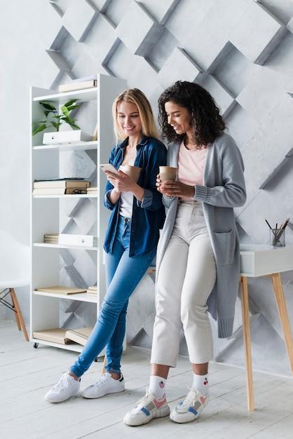 Mujeres jovenes felices que beben el café en oficina Foto gratis