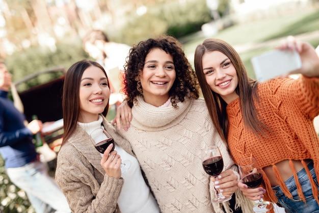 Las mujeres jóvenes hacen selfie durante un picnic con amigos. Foto Premium